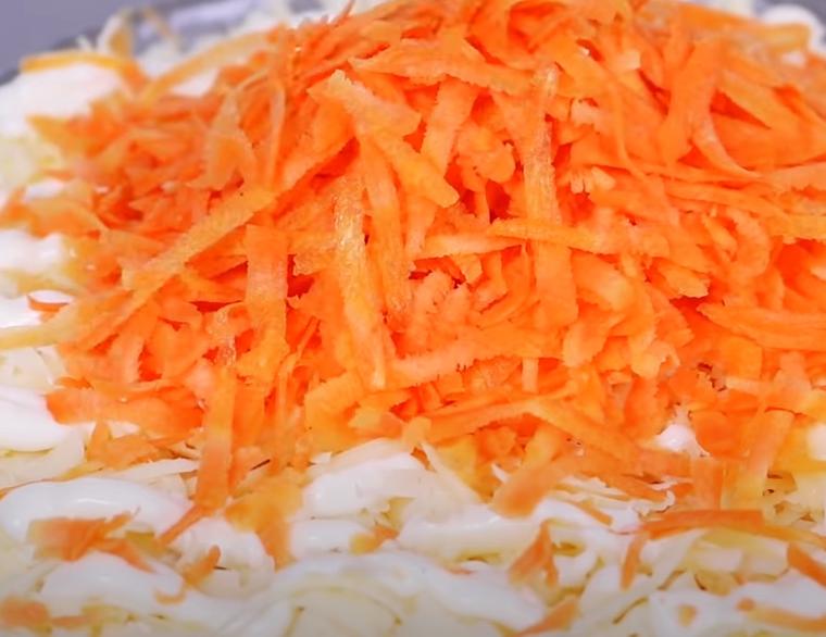 Натертую свежую морковь выложить поверх сыра и равномерно распределить